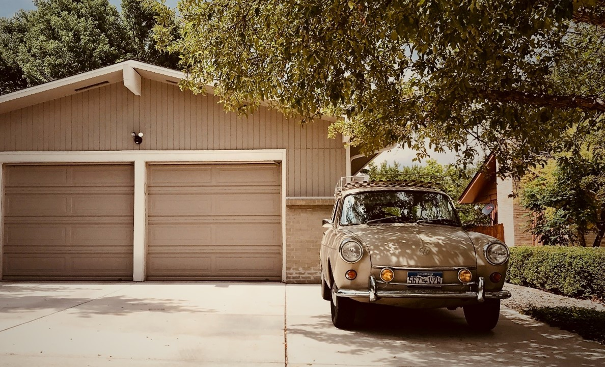 An old car parked in the driveway of an American house
